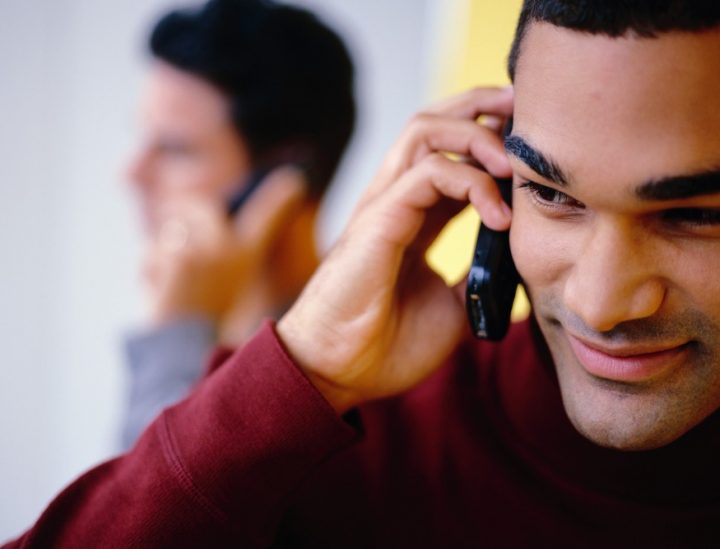 Young Man on the Phone Communication, Technology, Horizontal, Indoors, Facial Hair, Stubble, Head And Shoulders, Human Hand, Mobile Phone, Smiling, Listening, One Person, Young Adult, 20s, Color Image, People In The Background, One Young Man Only, One Man Only, Portrait, Photography, On The Phone, Wireless Technology, Adults Only